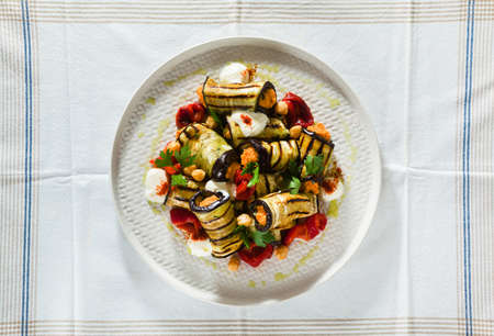 grilled eggplant wrap with red bell pepper hummus and spicy yogurt on the table. delicious vegan recipe 版權商用圖片 - 154098679