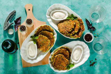 salted pancakes with zucchini and chickpea flour with spicy yoghurt sauce with beer on the table. summer vegan snack for family or lunch for friends