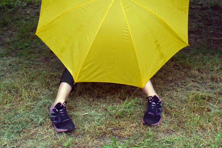 yellow umbrella and legs are visible