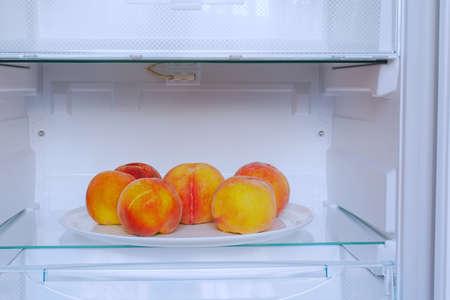ripe peaches on white plate in refrigerator