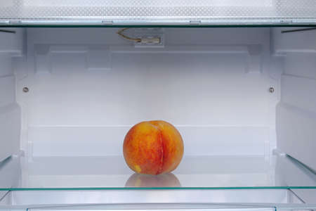 ripe peach on shelf in refrigerator
