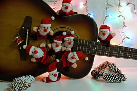 group portrait of funny santa claus toys on the background of old acoustic guitar