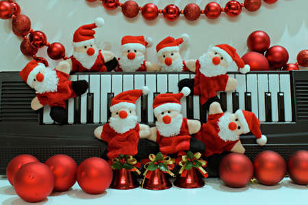 funny santa claus toys on blurred background of piano and christmas garland