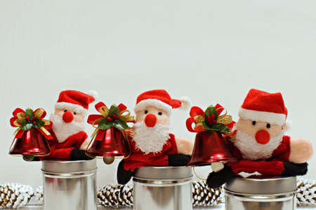 three funny santa claus toys with christmas bells on white blurred background