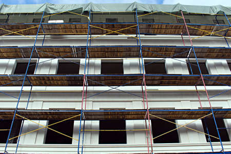 construction of a house with installed scaffolding for finishing the building facade