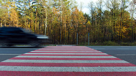 motion blurred image of super fast driving car on road crosswalk Stock Photo