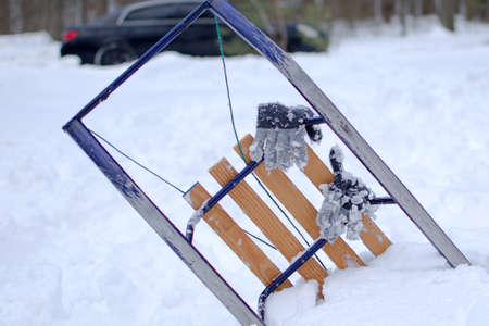 mittens gloves of a child with stuck ice hanging on sled against blurred background of white snow