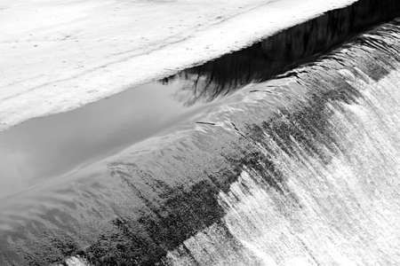 melting ice on river turns into stormy stream of falling water Imagens