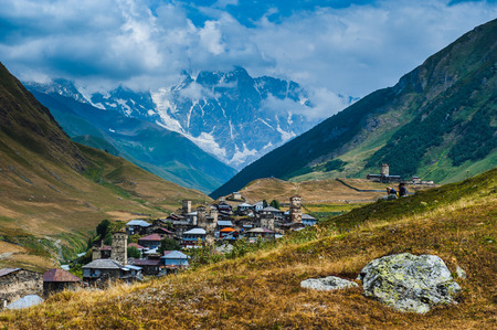 Village Ushguli landscape with massive rocky mountains Bezengi wall, Shkhara on the background in Svaneti, Georgia
