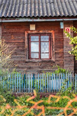 Facade of an old wooden house with a window in the village.