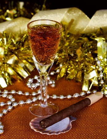 Crystal glass with brandy, cigars and Christmas decorations on a black background Stock Photo