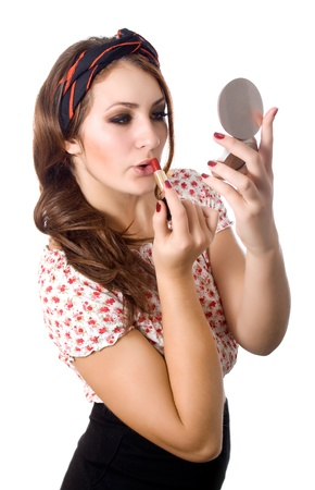 Young woman applying lipstick looking at mirror Stock Photo - 16695783