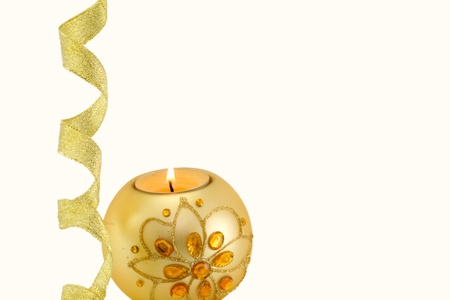 Candle with Christmas decorations and a golden ribbon at the bottom, on white background Stock Photo