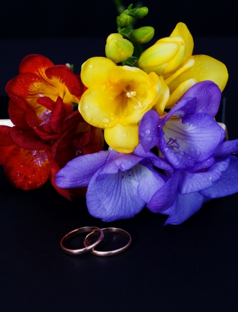 Wedding rings and a bouquet of freesias on a black background