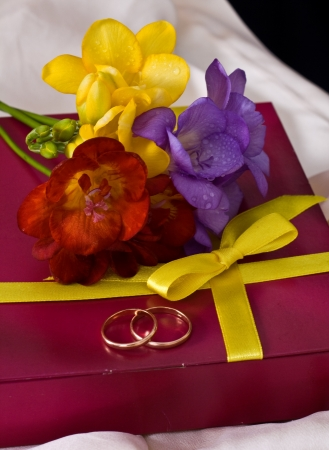 Bouquet of multicolored freesia, a gift from the wedding rings on delicate silk