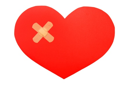 close up of a plasters and paper broken heart on white background  photo