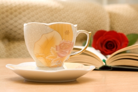 Cup of tea and an open book on the table with a rose