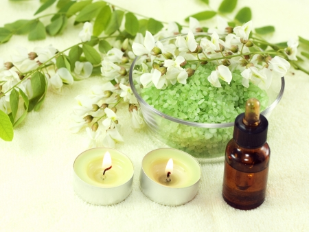 Fragrant flowers, acacia essential oils and candles on a yellow background