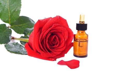Bottles of essential oil and red rose isolated