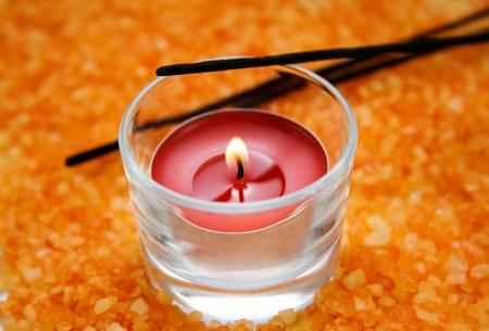 Räucherstäbchen und eine brennende Kerze auf dem Hintergrund von Badesalz