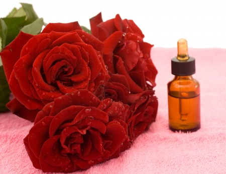Bouquet of red roses and rose oil on pink towel