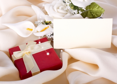 Holiday gift with a bouquet of the bride and a card on a gentle silk Stock Photo - 17150439
