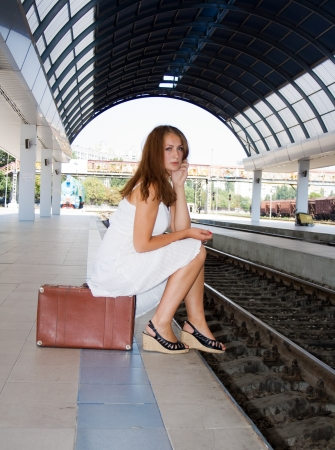 girl is sitting on a suitcase waiting for the train photo