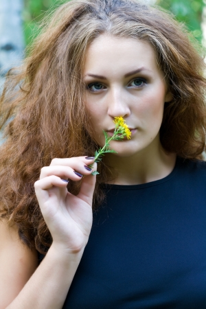preasure: Portrait of a beautiful girl with a yellow flower Stock Photo