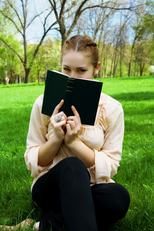 Woman hides her face behind a book sitting on green grass photo