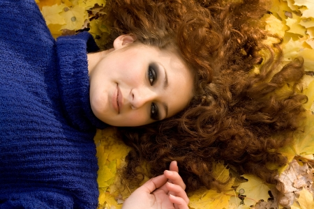 Young woman lying down in the fall leaves Stock Photo - 17275897