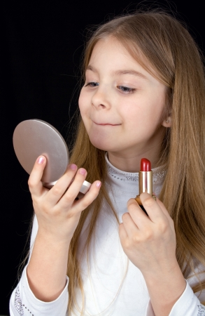 closeup portrait of the little girl with lipstick photo