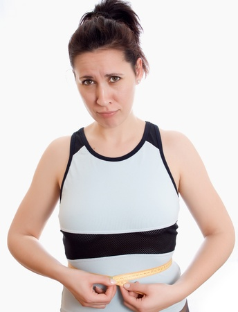 fatso: attractive woman measuring her waist measuring tape and the testimony of upset isolated Stock Photo