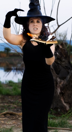 halloween witch  casts a spell over the burning book Stock Photo