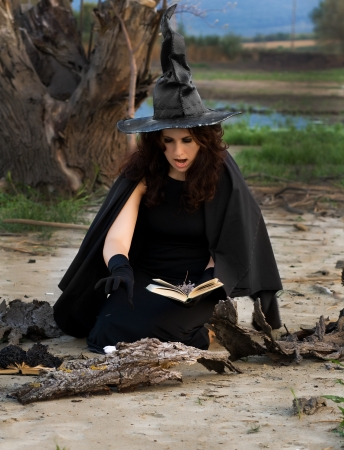 Witch conjures spells vychityvaya pronouncing them in a book Stock Photo - 17347089