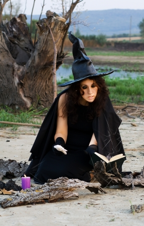 summon: Witch conjures spells vychityvaya pronouncing them in a book Stock Photo