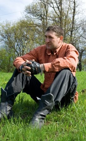 Young man sitting outside on grass in spring landscape Stock Photo