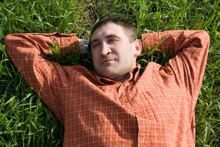 young man lying on the grass with his hands behind his head Stock Photo