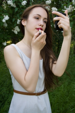 Girl applying lipstick on the lips Stock Photo - 17414761