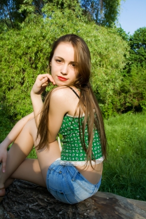 Pretty girl leaning against a tree in denim shorts and a t-shirt looks into the distance Stock Photo - 17414728
