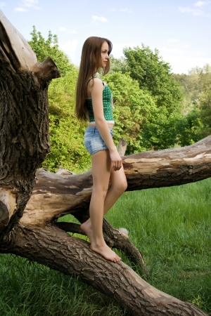 Pretty girl leaning against a tree in denim shorts and a t-shirt looks into the distance Stock Photo - 17405635