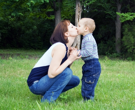 Mother kissing baby outdoors in the park Stock Photo - 17416869