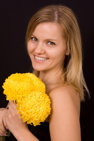 Romantic image of a young woman with yellow chrysanthemums. Stock Photo - 17419130