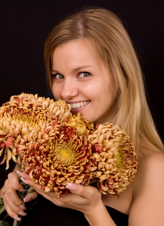 Romantic image of a young woman with yellow chrysanthemums. Stock Photo - 17419122