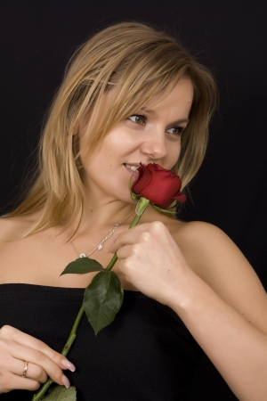 Beautiful woman smelling red bud of roses. Stock Photo - 17419023