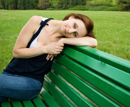 Girl in thought sitting on a park bench Stock Photo - 17449363