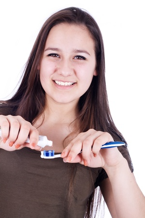 toothbrushing: Smiling woman with toothbrush squeezes the toothpaste Stock Photo