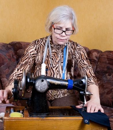 stitching machine: Senior woman using sewing machine at home Stock Photo