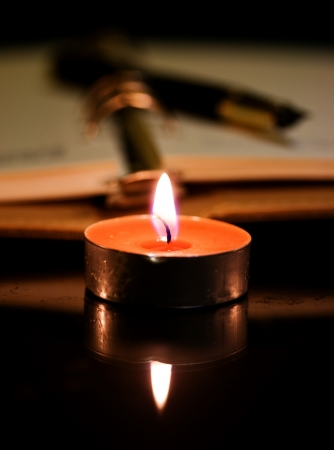 Open burning candle diary and pen photo