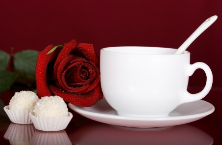 Romantic surprise in the form of a red rose, tea and chocolates photo