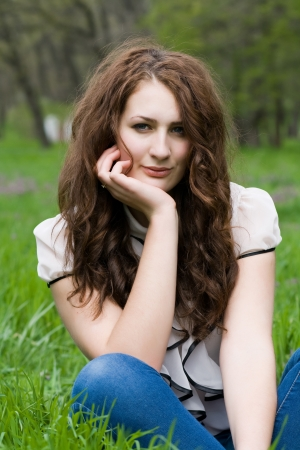 clothed: Beautiful and cute girl thoughtfully sitting on the green grass Stock Photo